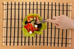Picture of hand with fork with greek salad. On the table Royalty Free Stock Photo