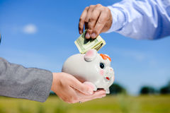 Picture of hands holding a piggy bank with a Royalty Free Stock Photos