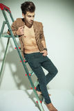 Picture of a handsome fashion man leaning to a ladder Stock Photo