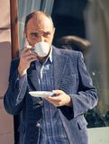 Man drinking a cup of coffee. Picture of handsome man walking on the street and looking aside while holding cup of coffee Royalty Free Stock Images