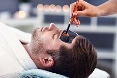 Handsome man having facial in spa salon royalty free stock images
