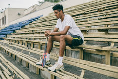 Picture of handsome young man on a bench. Man relaxing after tennis play. Man sitting on bench Royalty Free Stock Image