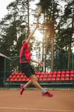 Picture of handsome young man on tennis court. Man playing tennis. Man throwing tennis ball. Beautiful forest area as Stock Photo