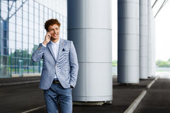 Picture of handsome young redhaired businessman talking on phone smiling Stock Photography