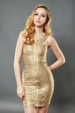Picture of happy beautiful young woman wearing gold dress posing Stock Images