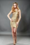 Picture of happy beautiful young woman wearing gold dress posing Stock Photography