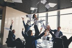 Happy business team celebrating victory in office. woman stand on table Stock Photos