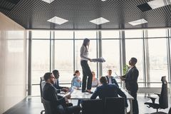 Happy business team celebrating victory in office. woman stand on table Stock Image