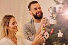 Happy couple decorating christmas tree Stock Photography