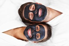 Happy couple having facial in spa salon stock image