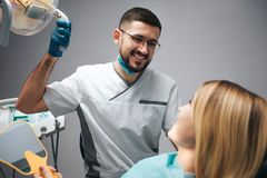 Picture of happy dentist sit beside client and look at look at her. He smile and hold lamp. Woman sit in chair and look stock images