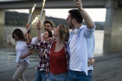 Picture of happy friends holding burning sparkles Royalty Free Stock Images
