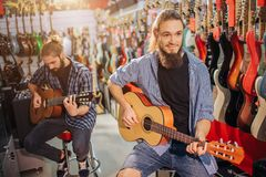 Picture of happy hipster sit on stool and smiling. He hold acoustic guitar in hands. Another young man sit and play as stock image
