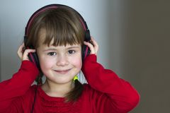 Picture of happy pretty child little girl with big headphones at home. Joyful child girl listening to music on gray blurred backgr. Ound. Home, technology and Stock Image