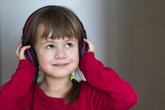 Picture of happy pretty child little girl with big headphones at home. Joyful child girl listening to music on gray blurred backgr. Ound. Home, technology and Stock Photos