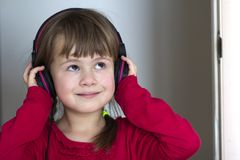 Picture of happy pretty child little girl with big headphones at home. Joyful child girl listening to music on gray blurred backgr. Ound. Home, technology and Stock Images