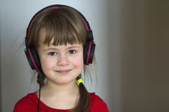 Picture of happy pretty child little girl with big headphones at home. Joyful child girl listening to music on gray blurred backgr. Ound. Home, technology and Royalty Free Stock Image