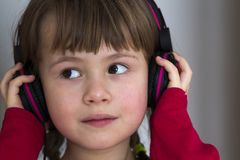 Picture of happy pretty child little girl with big headphones at home. Joyful child girl listening to music on gray blurred backgr. Ound. Home, technology and Royalty Free Stock Photo