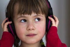 Picture of happy pretty child little girl with big headphones at. Home. Joyful child girl listening to music on gray blurred background. Home, technology and Stock Photos