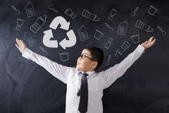 Happy schoolboy showing recycle sign stock photos