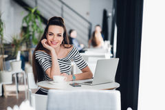 Picture of happy smiling woman using laptop in a cafe and looking at the camera. Stock Photo