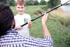 A picture of happy son standing in front of his dad and holding long fish-rod. Guy is holding it a bit. They are. Spending time together Royalty Free Stock Photo