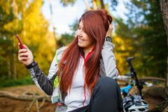 Picture of happy woman with cellular phone in autumn forest Stock Image