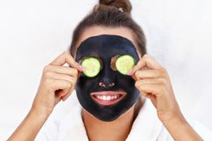 Happy woman having facial in spa salon stock photography