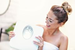 Happy woman holding bathroom scales in bathroom stock images
