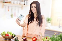 Happy woman preparing salad in modern kitchen. Picture of happy woman with vegetables in modern kitchen Stock Photography