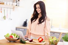 Happy woman preparing salad in modern kitchen. Picture of happy woman with vegetables in modern kitchen Stock Photo