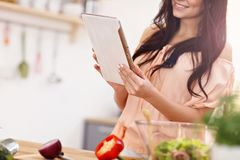 Happy woman preparing salad in modern kitchen and holding tablet. Picture of happy woman with vegetables in modern kitchen Royalty Free Stock Photography
