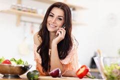 Happy woman preparing salad in modern kitchen. Picture of happy woman with vegetables in modern kitchen Royalty Free Stock Photos