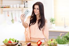Happy woman preparing salad in modern kitchen. Picture of happy woman with vegetables in modern kitchen Royalty Free Stock Photography