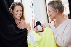 Happy woman shopping for clothes in store stock image