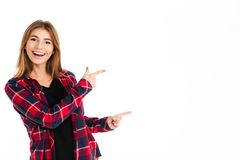 Happy young woman pointing to copyspace. Picture of happy young woman standing isolated over white wall background. Looking camera pointing to copyspace Royalty Free Stock Images