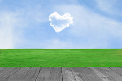 Picture of a heart cloud on blue sky in green field and wood pla. Nt Royalty Free Stock Photography