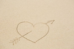 Picture of a heart pierced with an arrow on wet beach sand Stock Photos