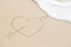 Picture of a heart pierced with an arrow on wet beach sand Royalty Free Stock Photos