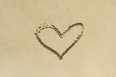Picture of a heart on the sand. Beach near the sea. Beautiful drawings on the yellow smooth sand. Leisure on the beach, romantic love Royalty Free Stock Image