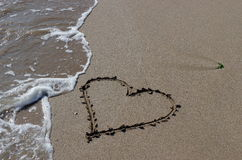 Seascape. Love, summer, sea, sun, beach, fun, holiday and a big heart on the sand Stock Photos