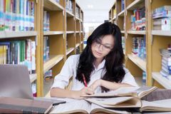 High school student girl studying in library. Picture of a high school student girl writing on a book while studying in the library Stock Images