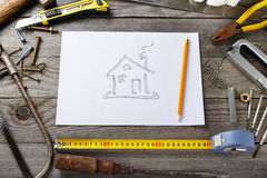 Picture of house on piece of paper with old tools Stock Photos