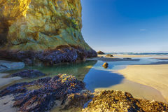 Arcadia Beach Oregon Coast. Picture of a huge boulders casting a shadow on tide pool on Arcadia Beach at the Oregon Coast Stock Images