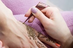 Picture of human hand being decorated with henna Tattoo. mehendi hand - beauty concept stock photos