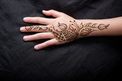 Picture of human hand being decorated with henna. Woman Hand with black cute henna mehendi designs stock photos