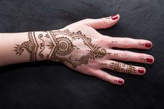 Picture of human hand being decorated with henna. Woman Hand with black cute henna mehendi designs stock image