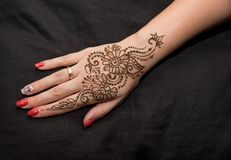 Picture of human hand being decorated with henna. Woman hand with black cute henna mehendi designs stock photography