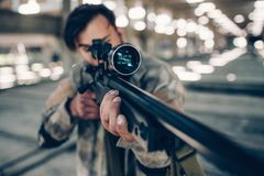 A picture if adult dark-haired man taking aim. He is using paintball rifle for that. He is playing paintball game. A picture if adult dark-haired man taking aim Royalty Free Stock Images