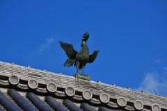 Hohou bird roof ornament, Kyoto Japan. Picture of an imaginal bird Hohou on the roof of old Japanese temple in Kyoto Japan, clear sky background royalty free stock photos